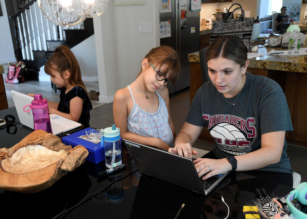Goolsby Elementary School second grader Ella Dweck, 7, takes an online class as Goolsby Elementary School second grader Odette Conrad, 7, is tutored by College of Southern Nevada student Jordyn Leal as Conrad takes an online class at her home during the first week of distance learning for the Clark County School District amid the spread of the coronavirus (COVID-19) on August 25, 2020 in Las Vegas, Nevada.