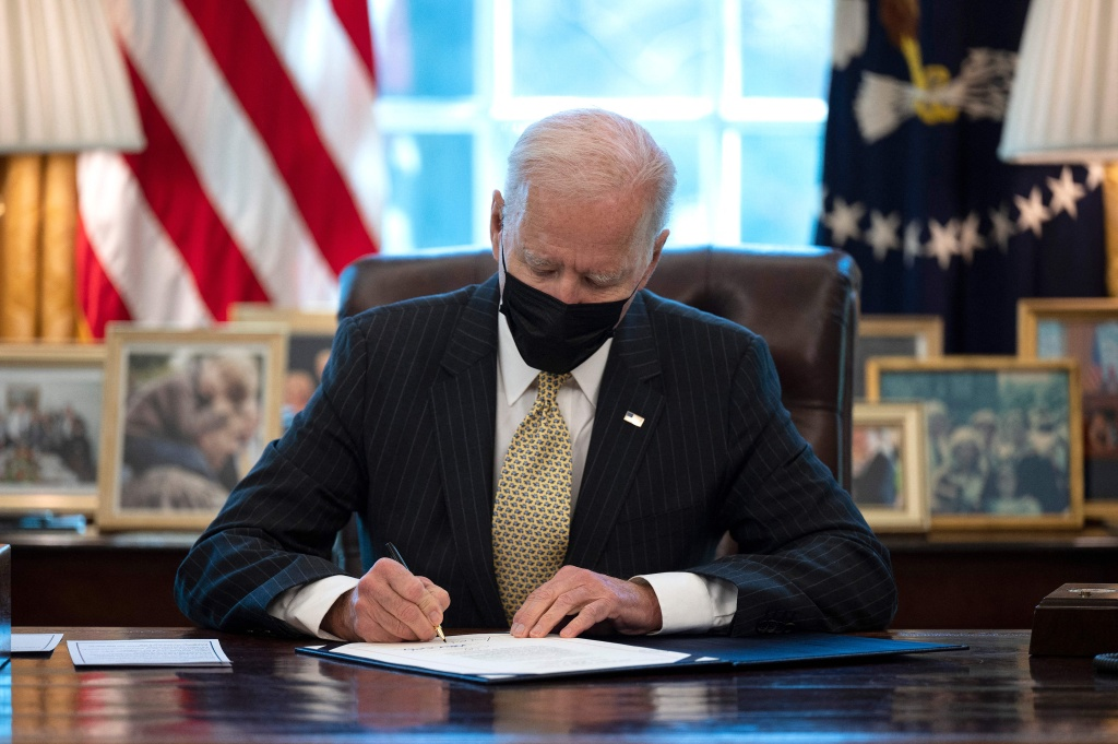US President Joe Biden signs the Paycheck Protection Program (PPP) Extension Act of 2021 into law at the White House in Washington, DC, on March 30, 2021.