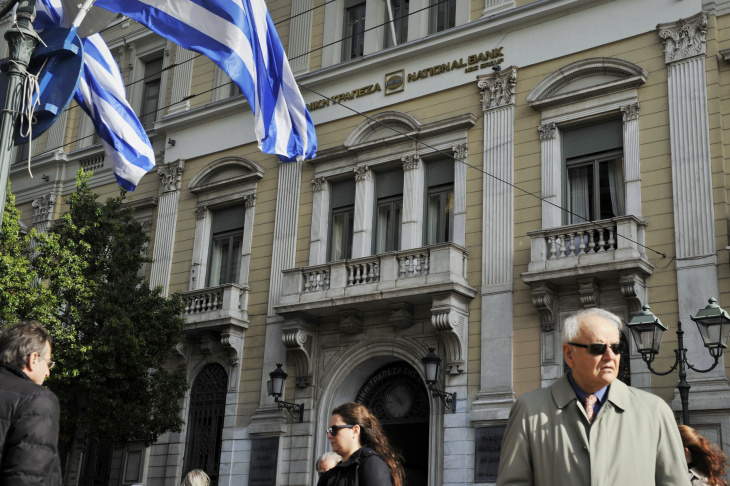People walk by a National Bank of Greece