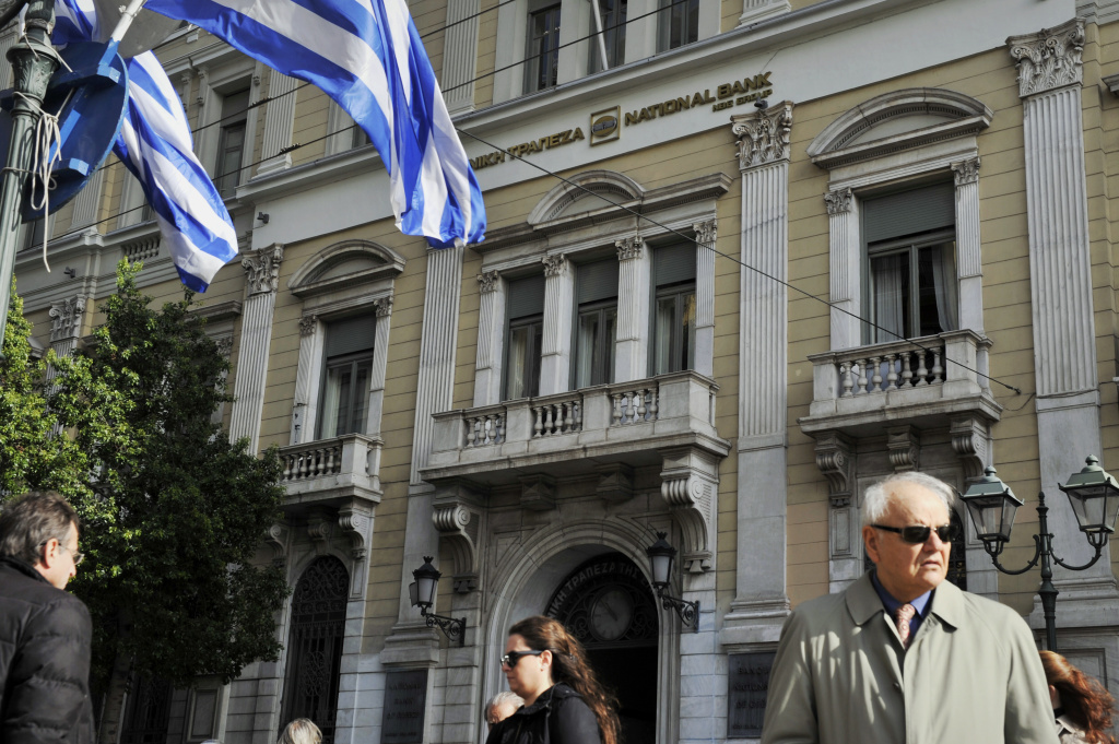 People walk by a National Bank of Greece  in Athens on October 27, 2011.