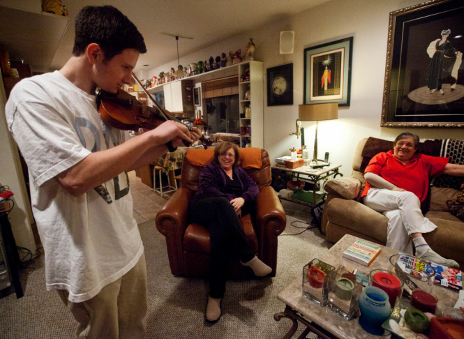 Seventeen-year-old Parker Sanchez-Engelmann plays violin on Thursday, Jan. 31 with his moms Alice Engelmann, left, and Cindy Sanchez. Sanchez-Engelmann is working to become an Eagle Scout.