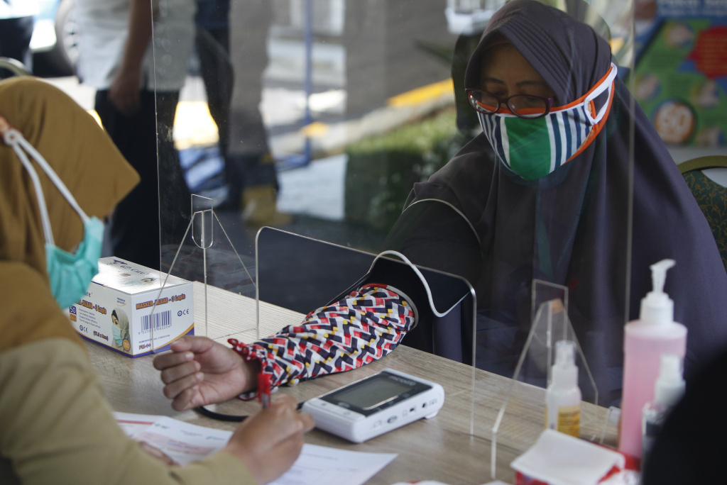 Health workers measure a woman's blood pressure during a simulation of a COVID-19 vaccine trial in Indonesia.