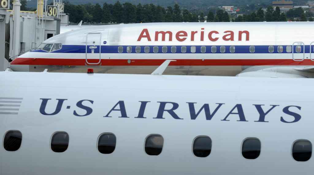 This Tuesday, Aug. 13, 2013 file photo shows an American Airlines plane and a US Airways plane parked at Washington's Ronald Reagan National Airport. On Tuesday, Nov. 12, 2013, the Justice Department said it had reached an agreement to allow the merger of the two airlines. The agreement requires them to scale back the size of the merger at key airports in Washington and other big cities.