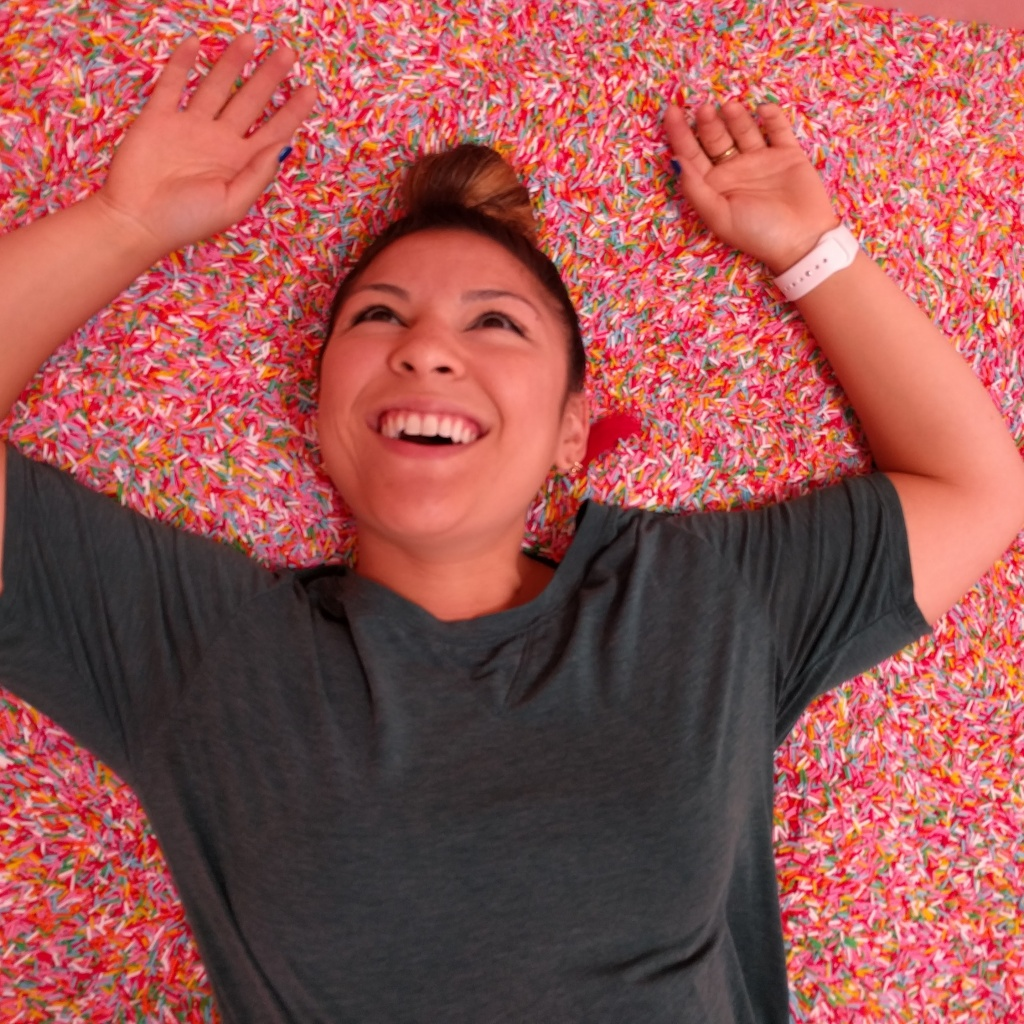 "KPCC's Maya Sugarman ""wades"" into the pool of rainbow sprinkles at the Museum of Ice Cream in Los Angeles."
