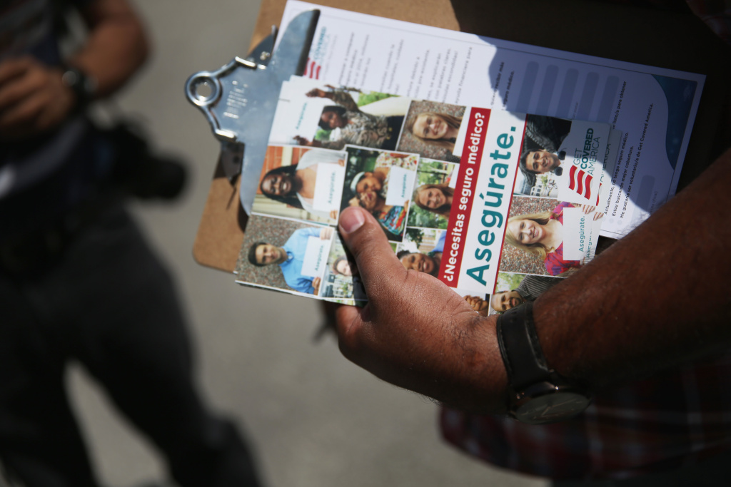 Milton Vazquez, an organizer for 'Get Covered America', stands with a clipboard at the Hialeah Literacy Fair September 14, 2013 in Hialeah, Florida. T