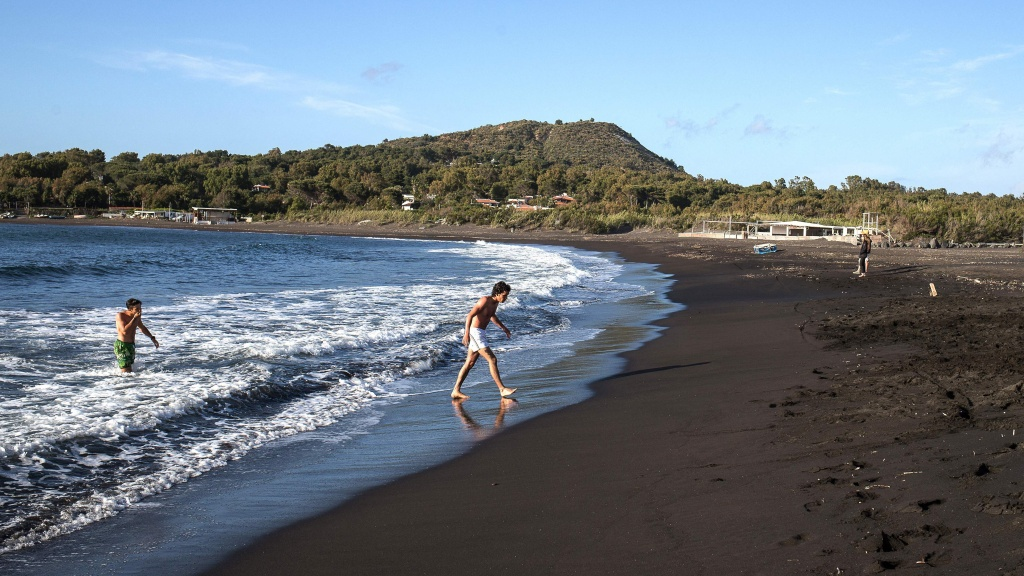 The European Union is poised to open travel to more visitors after ambassadors approved changes to travel restrictions Wednesday. Here, people walk out of the sea last week on Italy's volcanic island of Vulcano.