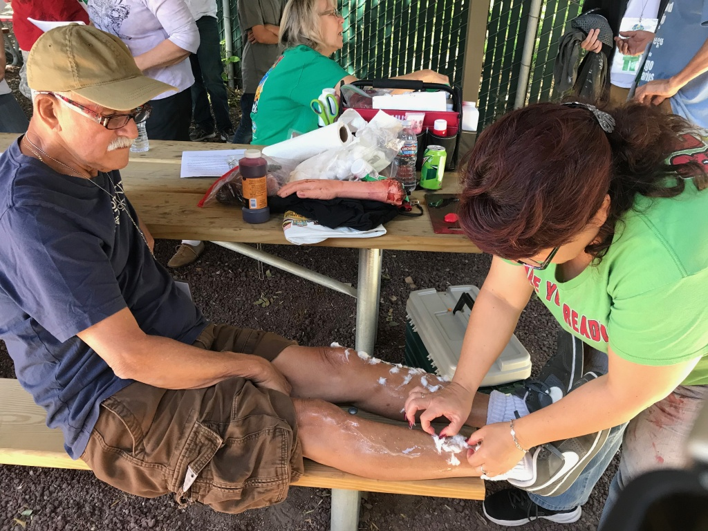 Moulage Artist Marie Sorensen paints and sculpts fake wounds on the volunteer victims. Here, Ernie Villa is getting fake third degree burns all over this body.