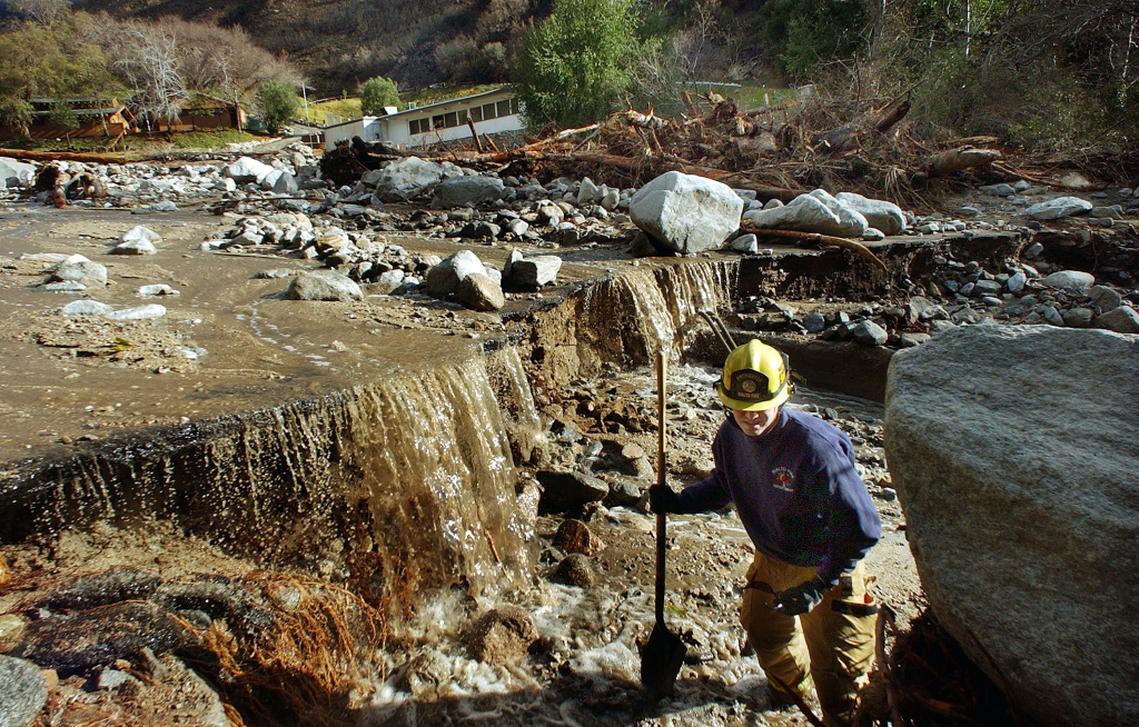 Rialto Firefighter Dave Denman searches for victims after a mudslide Dec. 26, 2003 in Waterman Canyon, California. The mudslide which killed at least four, and left 12 missing was caused by heavy rains.