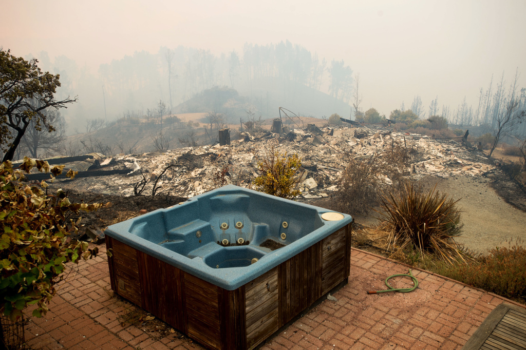 A hot tub rests in front of a residence leveled by the Loma fire along Loma Chiquita Road on Tuesday, Sept. 27, 2016, near Morgan Hill, Calif. More California residents were ordered from their homes Tuesday as a growing wildfire threatened remote communities in the Santa Cruz Mountains.