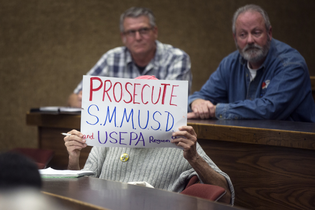 An attendee holds a sign during a question and answer session at a Pepperdine Law School town hall on PCBs in Malibu's public schools.