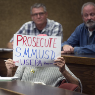 "An attendee holds a sign during a town hall meeting at Pepperdine University's law school on toxic PCBs inside Malibu public schools; reporting by KPCC's Stephanie O'Neill on the issue was part of the investigative program ""Reveal."""