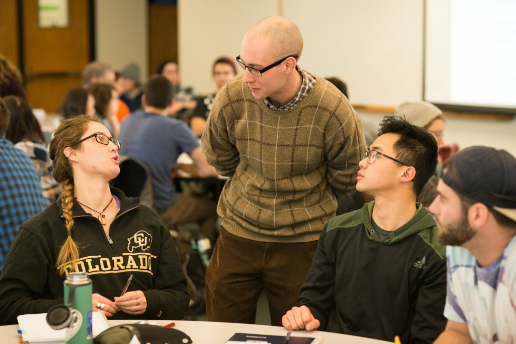 Learning assistant Michael Byars (standing) talks with (from left) students Anna Eydinova, Aaron Higa and Austin Reed during an evolutionary biology class.