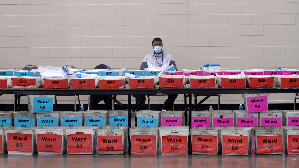 An election official pauses during the ballot recount earlier this month at the Wisconsin Center in Milwaukee. Officials in Milwaukee County, where President Trump had demanded a recount, said that Joe Biden's lead increased slightly on review.