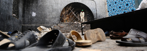 A Pakistani devotee looks at wreckage the day after a suicide bomb attack at a Sufi shrine in Lahore. Two suicide bombers blew themselves up in the Islamic shrine packed with worshippers on July 1, killing at least 37 people and wounding scores more.