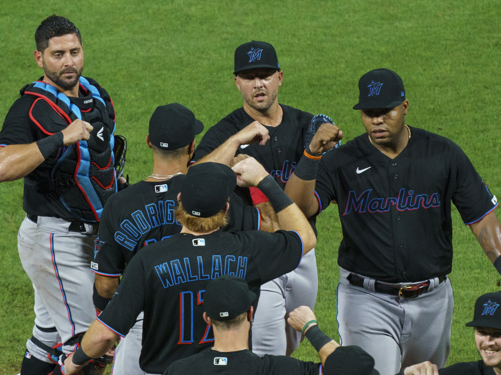 Members of the Miami Marlins celebrate a win with teammates against the Philadelphia Phillies on Friday. The Marlins game on Monday has been postponed.