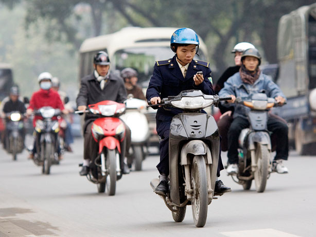 Motorcycles are the primary form of transportation in Vietnam, and public health officials are raising the alarm about a new road hazard: texting while driving. Here, a man checks his cell phone while driving in downtown Hanoi, Vietnam, in January.