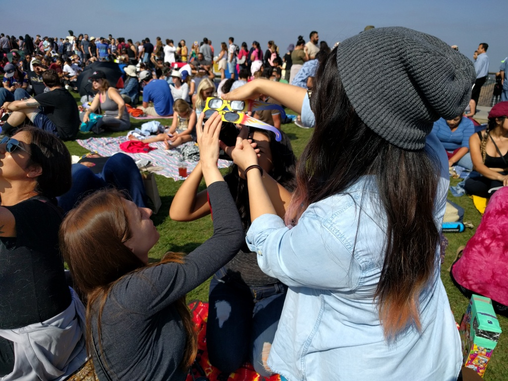 Iuliana Diaconescu, Gabriela Quiroz, and Jacqui Inouye work together to get the right pic of the eclipse on their DSLR camera