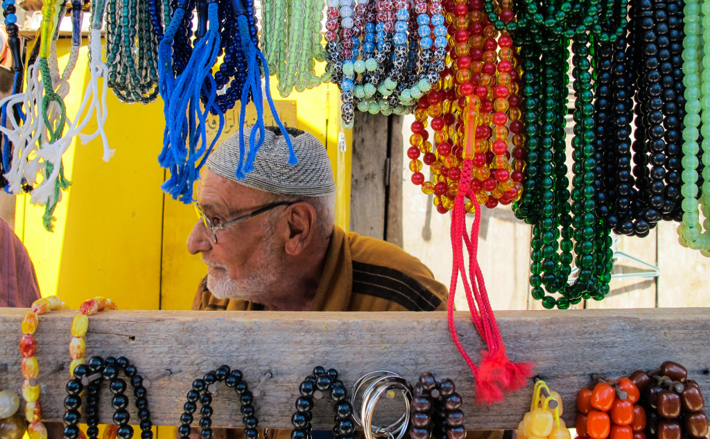 An elderly Iraqi man sits at a stall selling prayer beads hanging in the Souq al-Jumaa Friday market in Baghdad's Al-Rashid Street, on July 28, 2017.