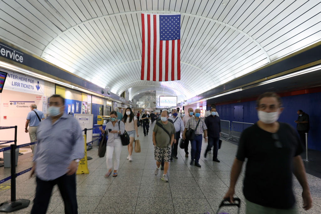 People walk through Pennsylvania Station as city workers attempt to hand out information sheets to travelers arriving by train from states affected by rules requiring 14-day quarantines on August 06, 2020 in New York City.
