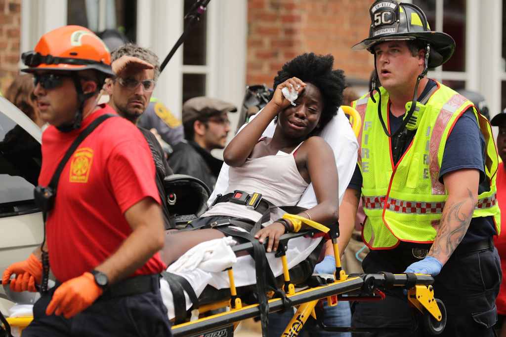 Rescue workers move victims on stretchers after a car plowed through a crowd of anti-fascist counter-demonstrators protesting a white nationalist rally on August 12, 2017 in Charlottesville, Virginia.