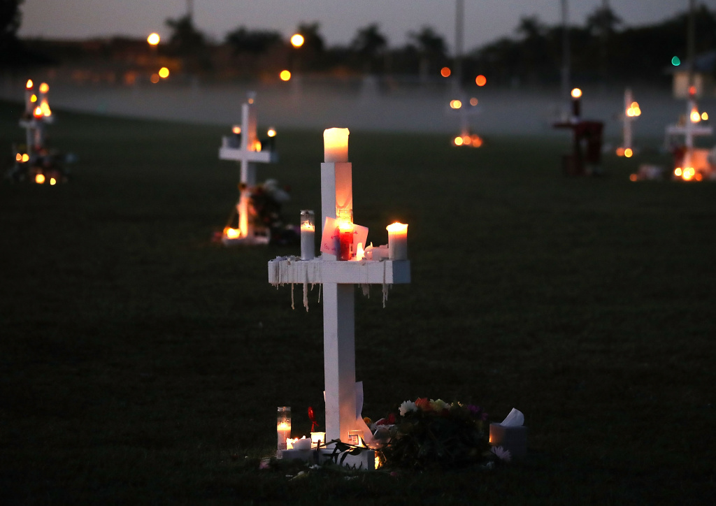 Candles glow at a memorial site to honor 17 people who were killed in the February 14, 2018 shooting at Marjory Stoneman Douglas High Schoo in Parkland, Florida.