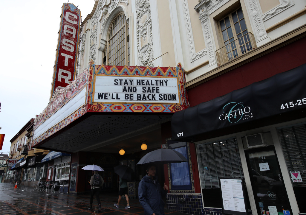 Pedestrians walk by the Castro Theatre that has a marquee announcing that they are closed due to a statewide ordinance banning gatherings of more than 250 people in San Francisco, California.