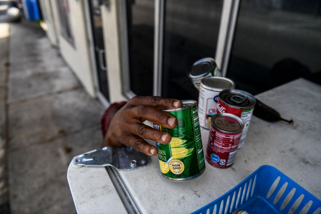 A mother of three children takes free food from a community refrigerator in Miami, Florida.
