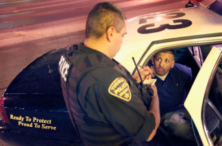 Leon Gutierrez, of the Tucson Police Department's Gang Tactical Unit, questions a suspect about his possible gang affiliation following an altercation outside a currency exchange on June 3, 2010 in Tucson, Arizona.