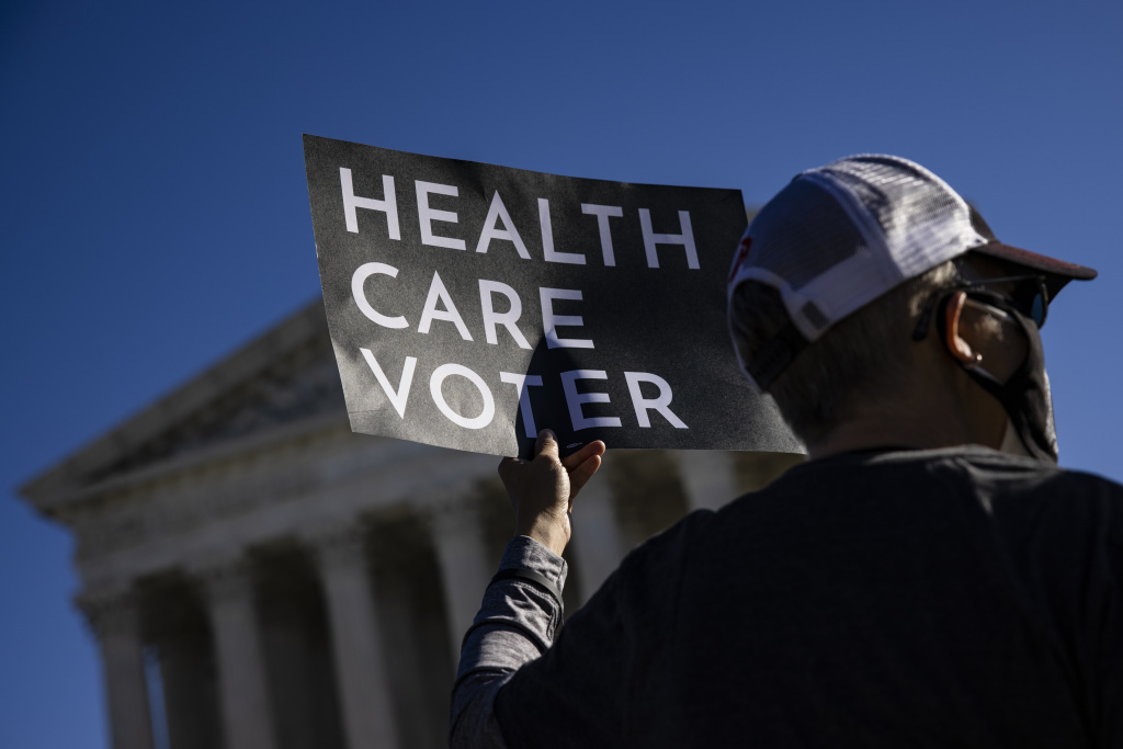 A supporter of the Affordable Care Act (ACA) stands in front of the Supreme Court of the United States as the Court begins hearing arguments from California v. Texas about the legality of the ACA on November 10, 2020 in Washington, DC.
