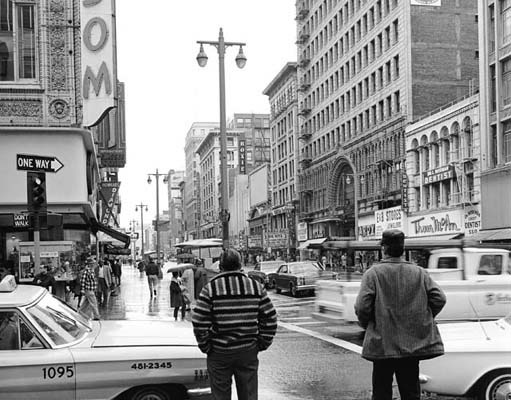 1966: In downtown L.A., a pedestrian's view of Broadway, looking south from 6th Street on a rainy day. (Photograph courtesy of the Los Angeles Public Library)