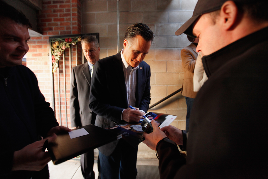 Republican presidential candidate and former Massachusetts Gov. Mitt Romney stops to autograph photographs during a campaign event at Elly's Tea and Coffee December 28, 2011 in Muscatine, Iowa. Romney began a three-day bus tour of Iowa with less than a week to go before the state's all-important caucuses.