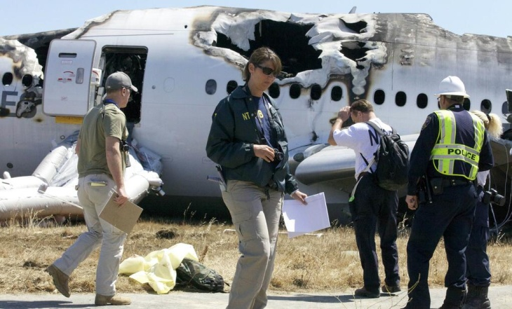 A NTSB investigator photographs the tail of the 777 Boeing airliner that crashed Saturday at San Francisco International Airport.