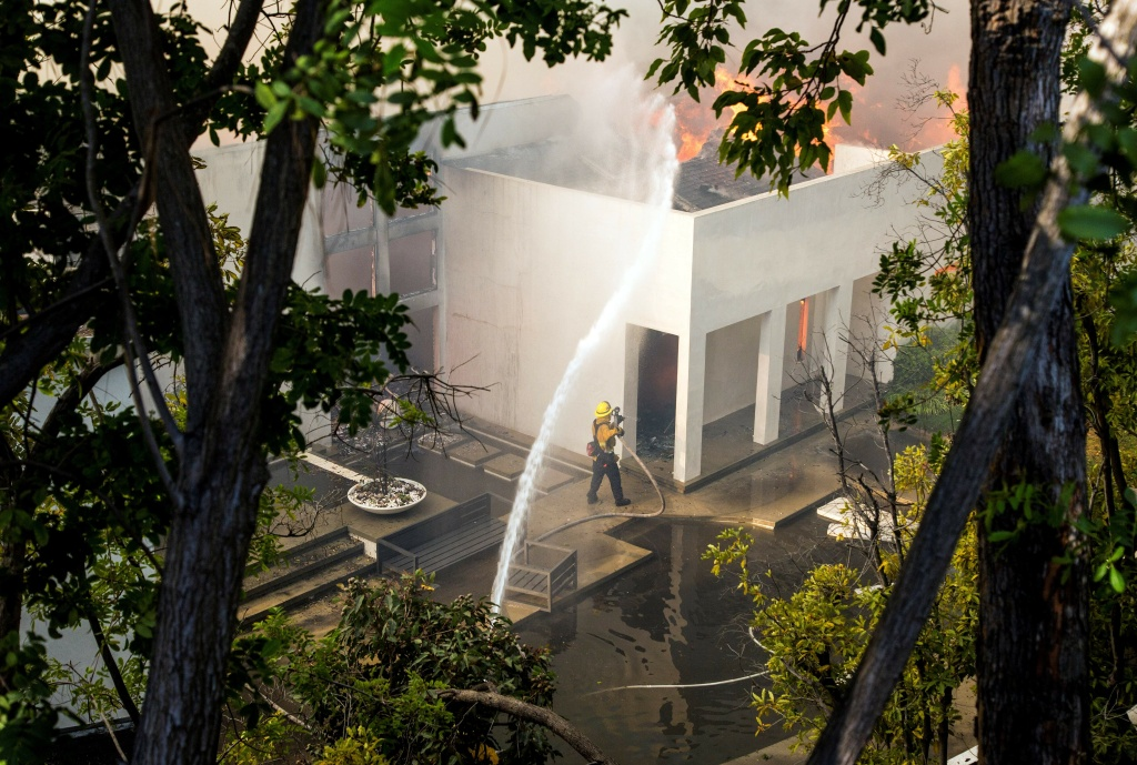 Firefighters work to save burning houses along Linda Flora Drive during the Skirball Fire in Los Angeles, California, in this December 6, 2017 file photo.