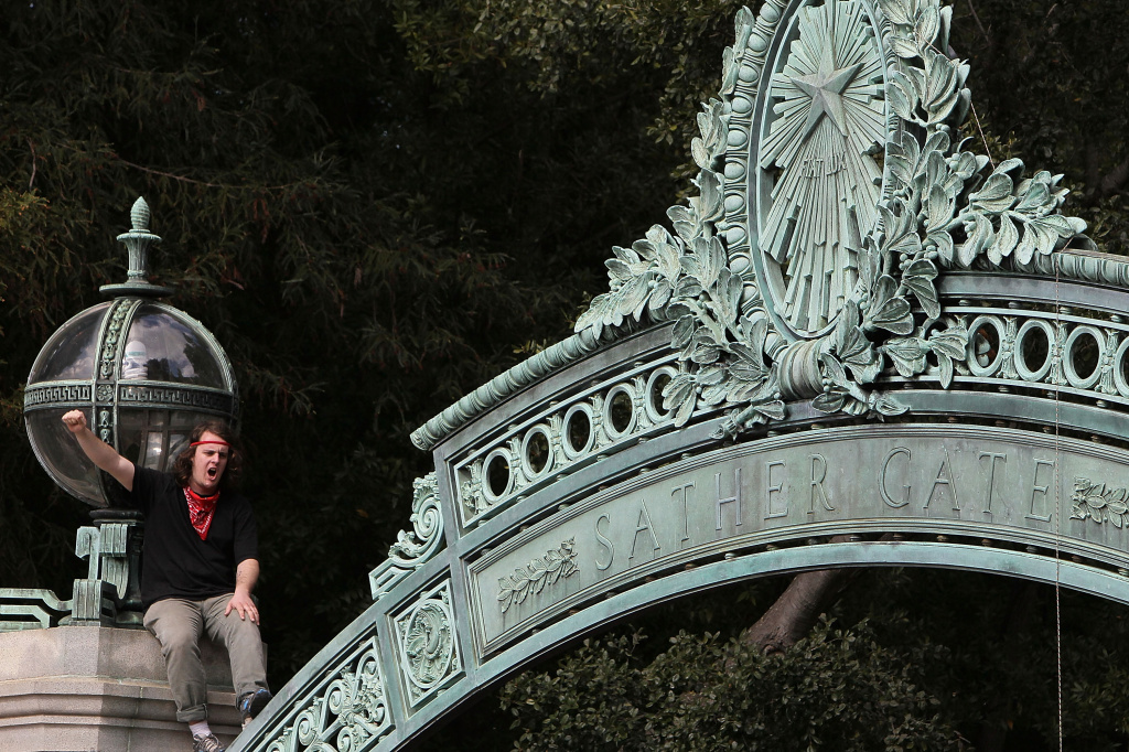 A student at UC Berkeley sits on top of Sather Gate as he participates in a demonstration during a national day of action against funding cuts and tuition increases March 4, 2010 in Berkeley, California. The campus was also a site for demonstrators during the anti-apartheid movement