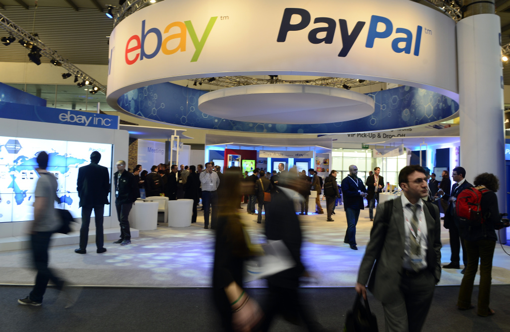 In this Wednesday, Feb. 27, 2013, file photo, attendees walk in front of an EBay and PayPal display area at the Mobile World Congress, the world's largest mobile phone trade show, in Barcelona, Spain. PayPal is splitting from EBay Inc. and will become a separate and publicly traded company during the second half of 2015.