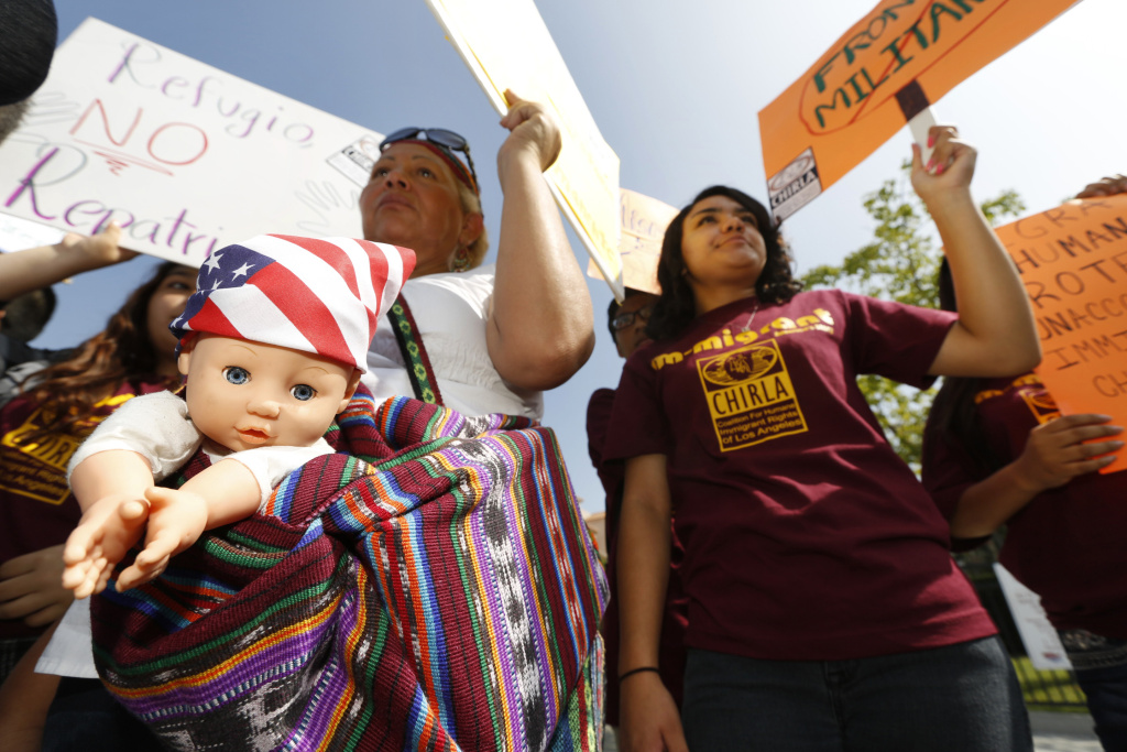Immigration activists Amarily Ortiz, left, and Mayra Sixtos, demand the Mexican government to take more measures to protect and respect the rights of unaccompanied minors and families crossing Mexico's territory during a protest outside the Mexican Consulate in Los Angeles Thursday, July 3, 2014. The United Nations is now pushing for many of the Central Americans fleeing to the U.S. to be treated as refugees displaced by armed conflict, a designation meant to pressure the U.S. and Mexico to accept tens of thousands currently ineligible for asylum.