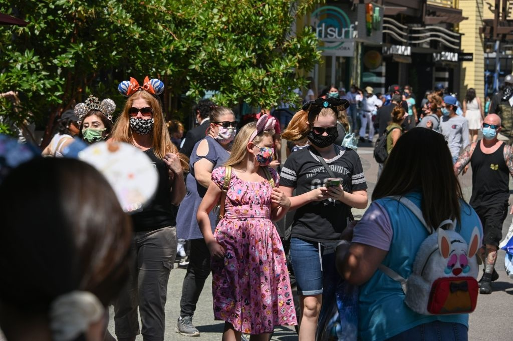 People visit Downtown Disney in Anaheim, California on July 9, 2020, the first day the outdoor shopping and dining complex has been open to the public since it closed in mid-March amid the COVID-19 pandemic.
