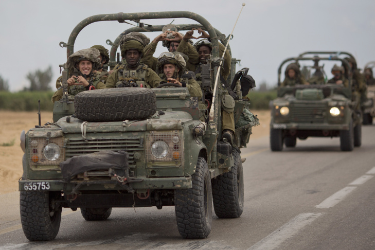 Israeli soldiers smile as they ride on a military vehicle near the Israel-Gaza Border, Thursday, July 17, 2014. Israel and Hamas have begun observing a five-hour humanitarian cease-fire, as fighting extended into a 10th day. The two sides agreed to the pause following a request by the United Nations so that supplies could be delivered to Gaza.(AP Photo/Ariel Schalit)