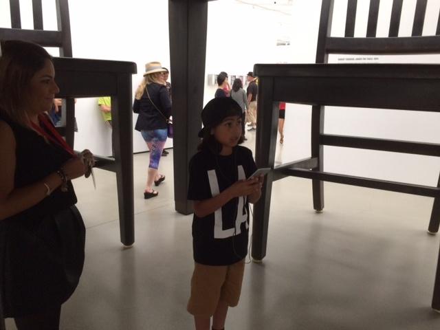 Noah, 10, listens to LeVar Burton's audio tour while standing
