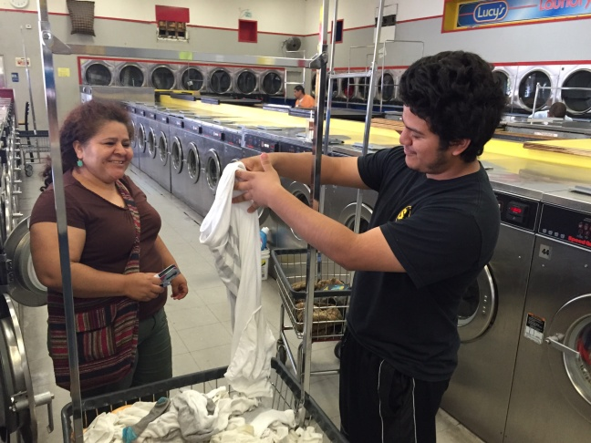 Jerry Aguirre does the laundry with his mother Elia at Lucy's Laundromat.