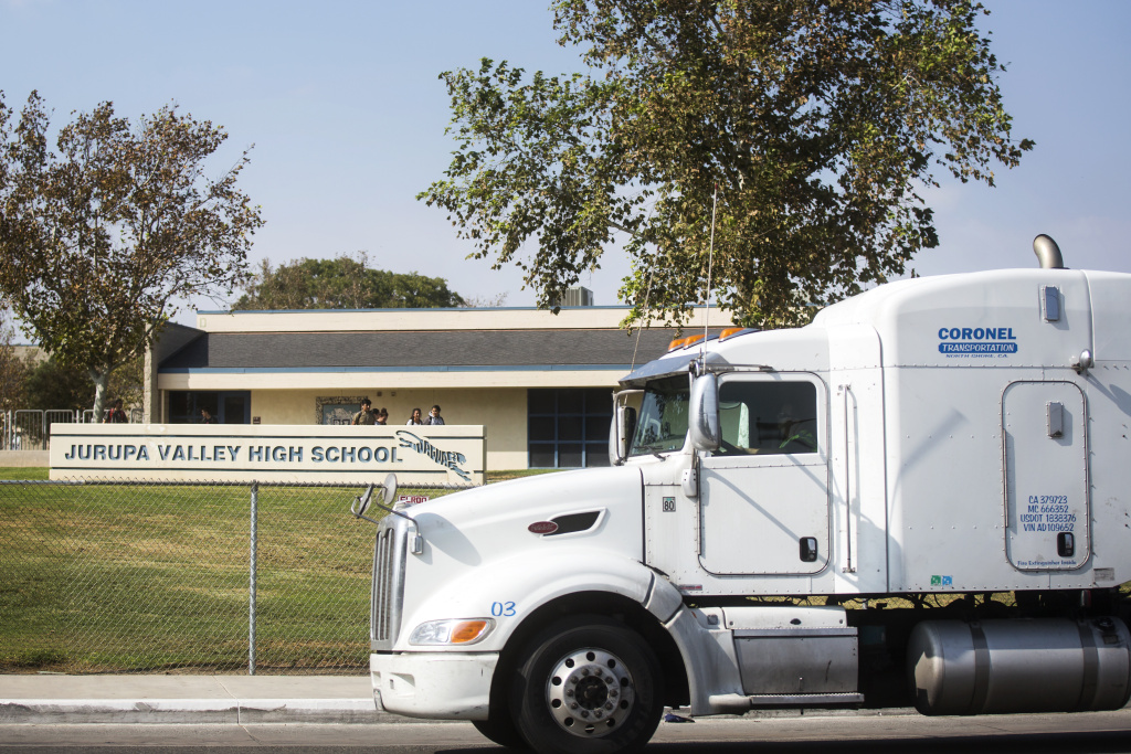 A truck passes Jurupa Valley High School after school. Long-term studies of the Inland Empire show that pollution is high in communities with significant concentrations of warehouses and diesel trucks.