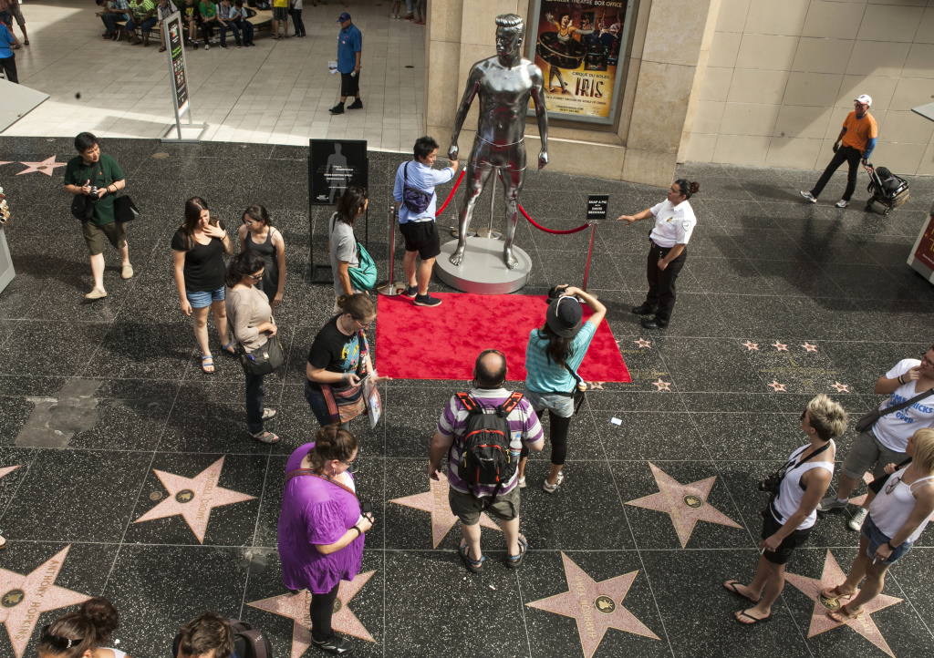 In this file photo taken Aug. 17, 2012, tourists take photos with a 10-foot statue created and modeled after English soccer star David Beckham displayed in the Hollywood section of Los Angeles. The intersection of Hollywood and Highland is the crossroads for the Hollywood Walk of Fame, where more than 2,400 terrazzo-and-brass stars containing the biggest names in the entertainment business can be viewed by just walking down the sidewalk. (AP Photo/Damian Dovarganes, File)