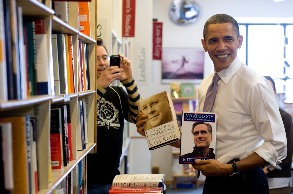 US President Barack Obama holds up copies of Karl Rove's book and Mitt Romney's book at the Prairie Lights Bookstore during an unscheduled stop in Iowa City, Iowa, March 25, 2010.
