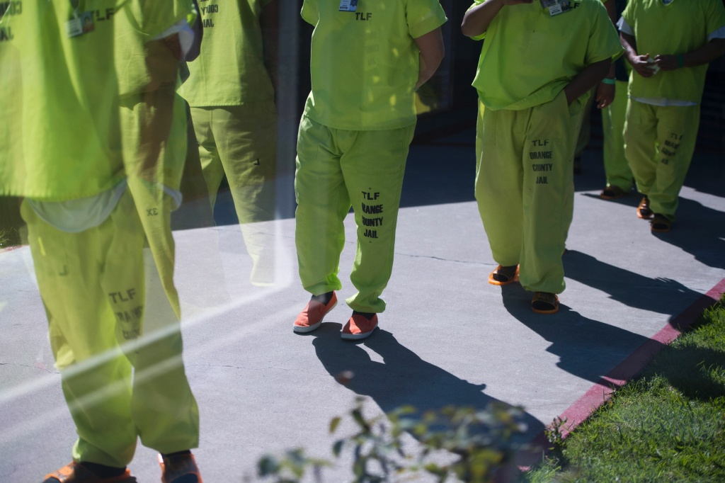 FILE PHOTO: Men wearing neon-colored jail clothes signifying immigration detainees walk to pick up their lunches at the Theo Lacy Facility, an Orange County jail that houses convicted criminals as well as immigration detainees.