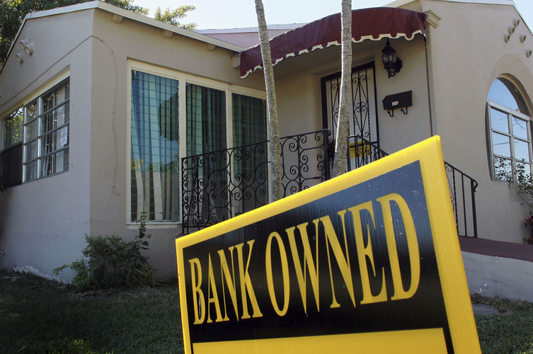 A bank-owned sign is seen in front of a foreclosed home.