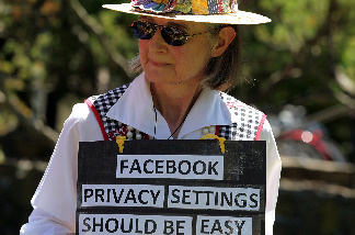 Mary Guedon of the group Raging Grannies holds a sign as she protests outside of the Facebook headquarters June 4, 2010 in Palo Alto, California.