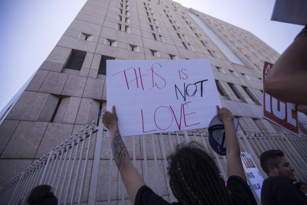 People demonstrate and call out words of encouragement to detainees held inside the Metropolitan Detention Center after marching to decry Trump administration immigration and refugee policies on June 30, 2018 in Los Angeles, California.