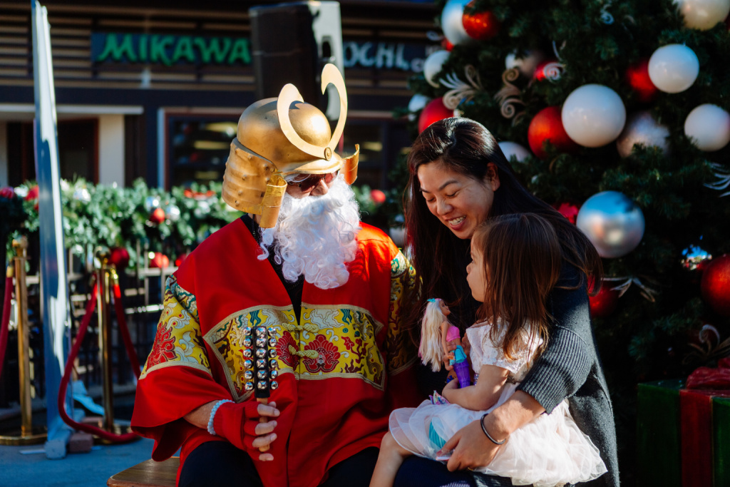 Mike Okamoto poses as Shogun Santa with visitors to Japanese Village.