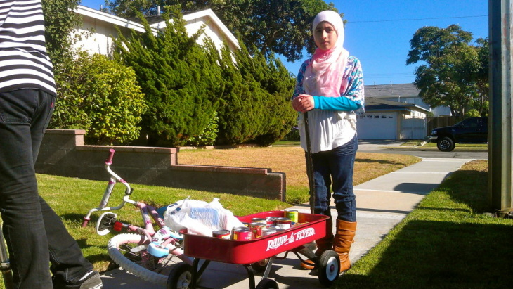 Keya stops the wagon in front of a neighbor's house.