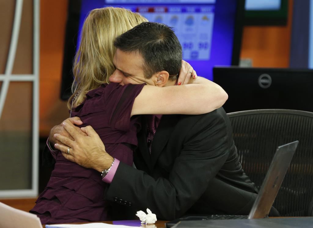 WDBJ-TV7 news morning anchor Kimberly McBroom, left, hugs meteorologist Leo Hirsbrunner after their early morning newscast at the station, Thursday, Aug. 27, 2015, in Roanoke, Va. Reporter Alison Parker and cameraman Adam Ward were killed during a live broadcast Wednesday, while on assignment in Moneta. (AP Photo/Steve Helber)